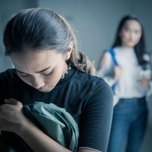 Kuvassa etualalla oleva tyttö on pää painuksissa ja taustalla kaksi tyttöä katsoo häntä kohti.
