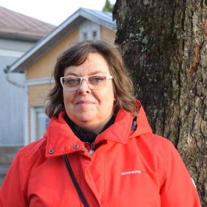 En kvinna med röd jacka och glasögon poserar ute vid ett större träd inne i en stad.