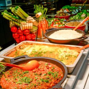 Ett buffébord med grönsaker och mat i lådor och skålar.