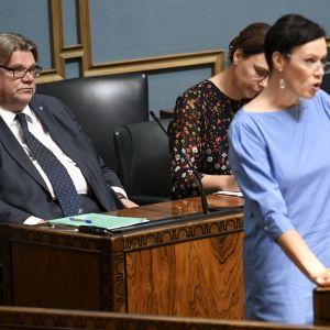Maarit feldt-Ranta talar i riksdagen med Timo Soini bakom sig.