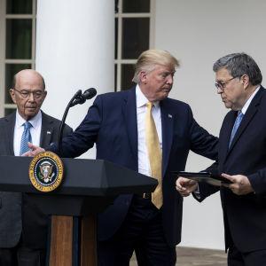 Donald Trump håller handen på Bill Barrs axel och ger honom ordet, Wilbur Ross i bakgrunden.
