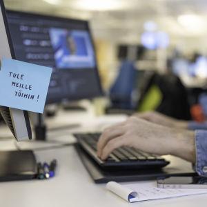 """""""Tule meille töihin"""" -tekstillä varustettu post-it lappu työpisteen näyttöön kiinnitettynä."""
