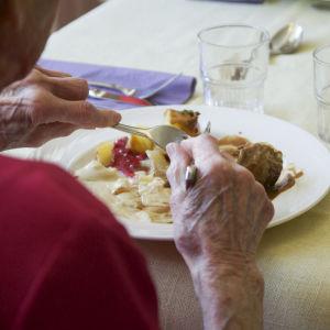 En bild på ett par äldre händer som äter mat med gaffel och kniv.