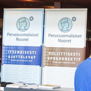 Två plakat med text på finska vid Sannfinländarnas partikongress i Åbo sommaren 2015