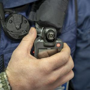 En hand håller i Polisens overallkamera fäst  på uniformen i höjd med hjärtat.