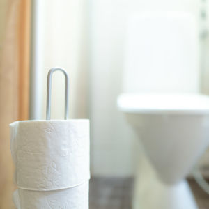 Toalettpapper i en ställning. I bakgrunden en wc-stol.