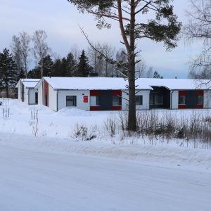 En radhus byggnad med vita och röda väggar. Framför byggnaden finns två träd.