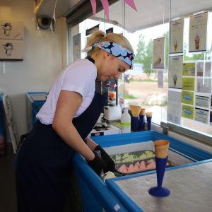 En ung kvinna med namnet Ursula Mantere arbetar som försäljare i en glasskiosk. I förgrunden syns en glassvåffla i en blå strut och Ursula håller på att skopa glass.