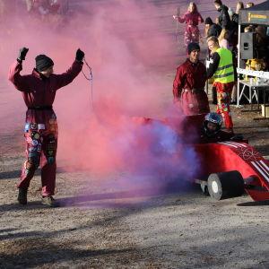 En paffversion av en racerbil har åkt ner för backen. Rödlila rök fyller området.