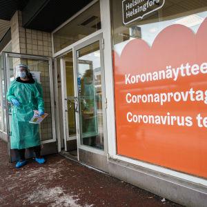 ¨Henkilökunnan edustaja pitää koronatestauspaikan ovea auki. Ikkunassa teksti koronanäytteenotto kolmella kielellä.