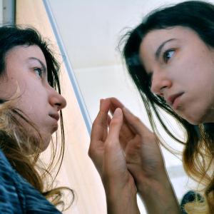 En allvarlig kvinna ser på sin egen spegelbild i ett fönster.