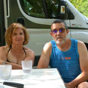 En kvinna och en man sitter vid ett bord framför en husvagn.
