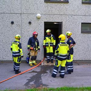 Brandmän utanför dörren till källaren där det läcker.