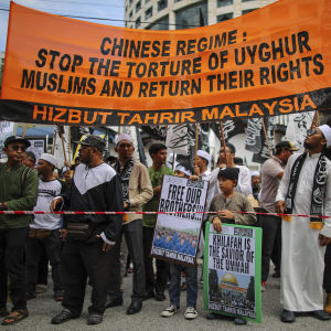Personer demonstrerar mot Kinas behandling av den muslimska uigurbefolkningen.