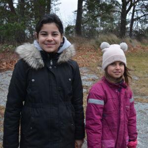 Två flickor står vid en gräsmatta.