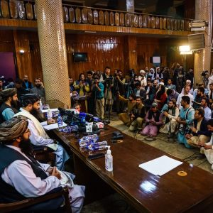 Talibanernas talesperson Zabihullah Mujahid talar inför en sal full med mest manliga representanter för medier i Kabul.