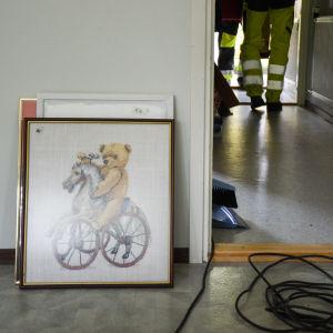 Korsstygnstavla med nallebjörn står på golvet lutad mot väggen.