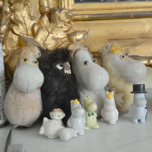 En grupp gamla dockor som föreställer olika karaktärer ur berättelserna om Mumintrollen står på ett spegelbord.