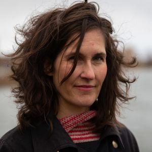Kirjailija Malin Kivelä seisoo ulkona. Taustalla meri.