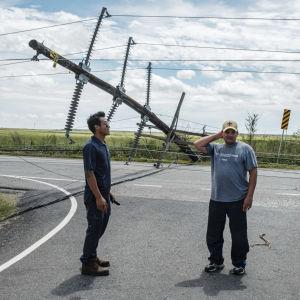 Miehet seisovat tiellä, taustalla kaatunut sähköpylväs