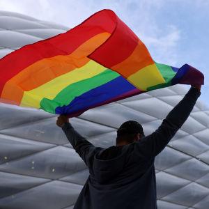 Fani sateenkaarilipun kanssa stadionilla ennen Saksan ja Unkarin kamppailua.