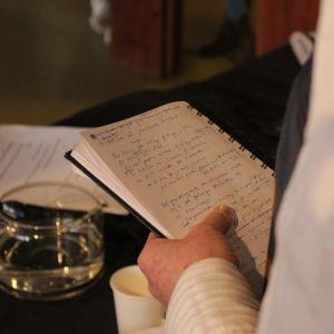 Kvinna läser text i ett anteckningsblock.
