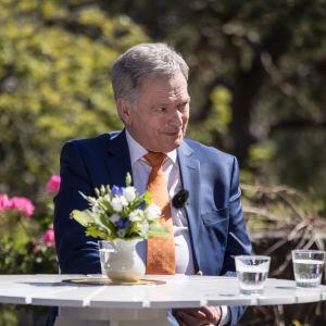 Leende Sauli Niinistö ute i solen bland blommorna på Gullranda.