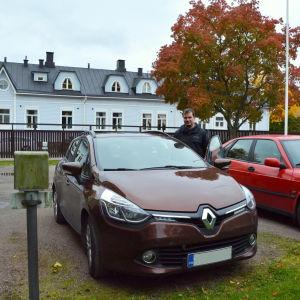 En brun och en röd bil står parkerade på en innergård.