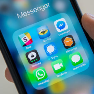 En ruta med olika appar (bland annat Whatsapp och Signal) på en telefonskärm. En hand håller i telefonen.