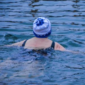 Kvinna med mössa på huvudet simmar