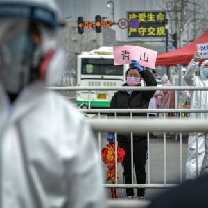 En kvinna håller upp en välkomstskylt till patienter som tillfrisknat från coronaviruset