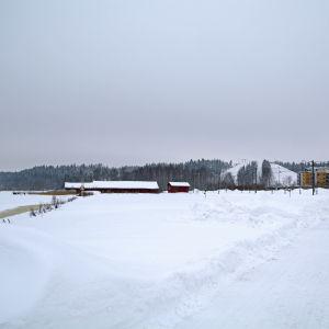 Västra åstranden i Borgå täckt av snö, i bakgrunden syns en skidbacke.