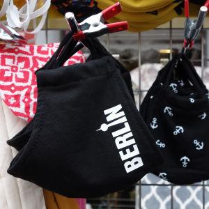 """Munskydd av tyg hänger i ett försäljningsstånd i Tyskland. På en skydden står det """"Berlin""""."""