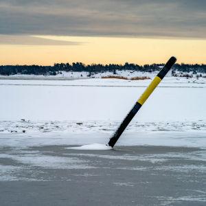 Ett sjömärke står snett på isen.