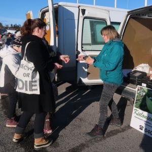 Familj köper matprodukter av en kvinna bakom en paketbil