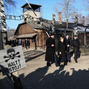 """Angela Merkel ja joukko muita ihmisiä kävelee keskitysleiriin """"Arbeit macht frei""""-kyltin ali."""
