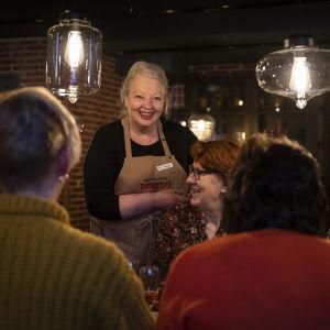 Hannele Hansson naureskelee pöydässä istuvien naisten kanssa.