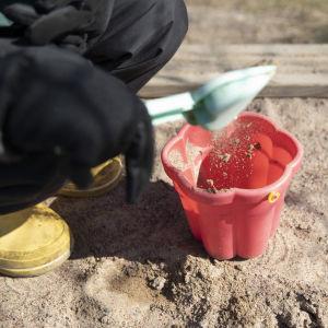 Ett barn häller sand i en hink i sandlådan.