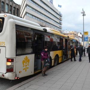 En dam med lila jacka stiger av en vitgul buss i Åbo centrum.