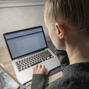 Ung person skriver studerar vid bärbar dator.