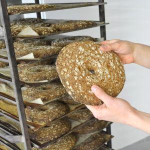 Färdiga rågbröd i ställning och en rund hålkaka i förgrunden.