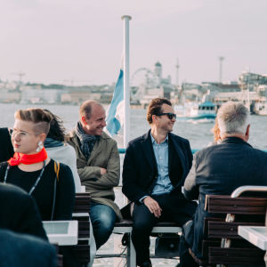 A group of people sitting on the outside deck of a ferry boat. Finnish flag and Helsinki waterline in the background.