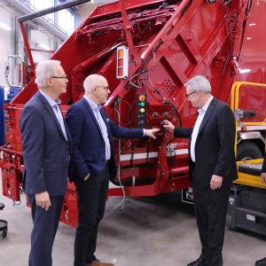 Fyra män står intill en röd sopbil.
