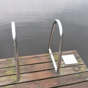 En bryggkant av trä  med badstege i rostfritt stål.