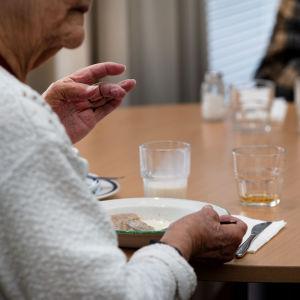 En äldre man äter på ett seniorcenter.