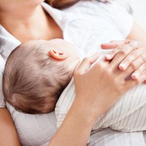 ett spädbarn som vilar på mammans bröstkorg. Mamman håller sina händer om den lilla barnkroppen
