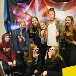 En grupp elever står bredvid pappfiguren Jontti Granbacka som leder MGP-showen i tv.