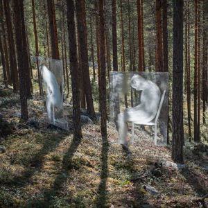 Läpikuultavia valkoisia hahmoja levyissä kiinnitettyinä puihin