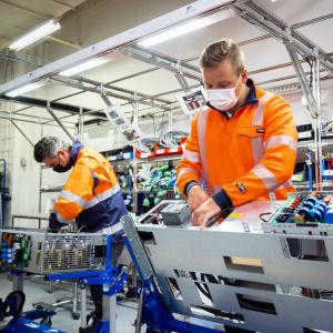 Kayvan Pournoori (vas.) ja Lauri Lehto (oik.) asentamassa sähkölaitetta Merus Powerin tehtaalla Nokia..a