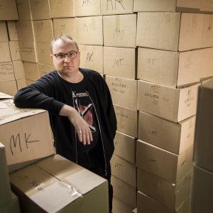Divarin pitäjä Elmeri Vehkala poseeraa WSOY:lta ostamiensa kirjalaatikkopinojen edessä 22.11.2018
